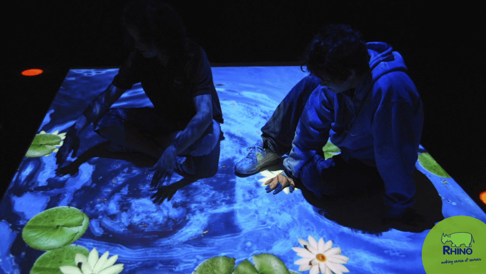 Children playing with an interactive projector on the floor