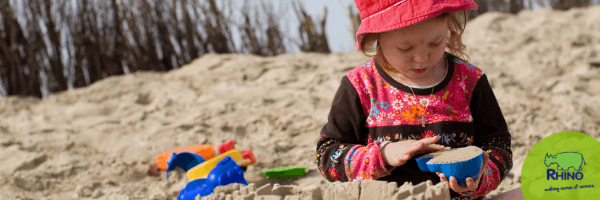 Child explores the texture of the sand.