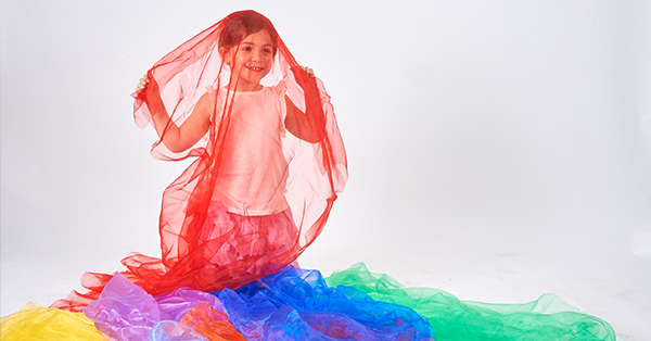 young girl plays with rainbow organza fabric