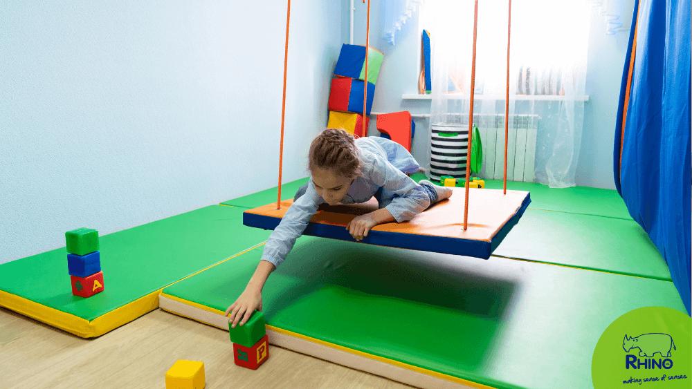 girl on platform swing in sensory integration room